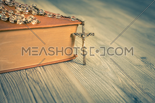 vintage rosary beads on old books,close up.