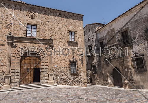Caceres, Spain - july 13, 2018: Episcopal Palace located in Plaza Santa Maria, main façade, Renaissance style, has a half-point arch pontoon adorned by a double row of ashlars, Caceres, Spain