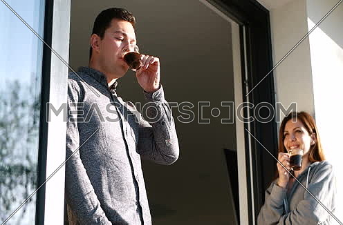 Casual Couple Enjoy Drinking Coffee On Terrace In The Morning