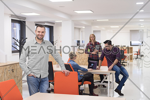 portrait of young businessman in casual clothes at modern  startup business office space,  team of people working together in background