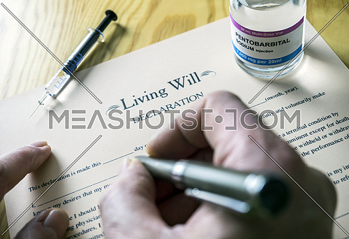 Living will declaration form Next to a vial of pentobarbital sodium to proceed to euthanasia, conceptual image