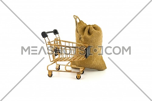 Empty golden shopping cart and jute bag isolated on white background
