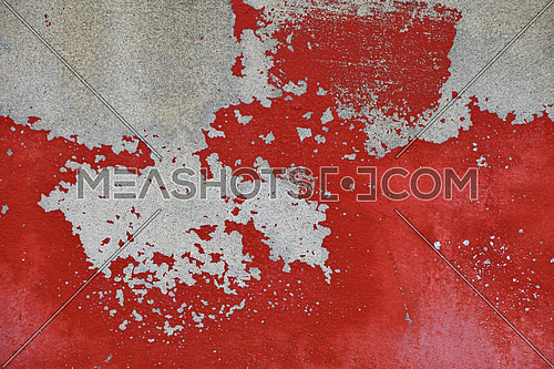 Flakes of old vintage grungy bright vivid red paint on grey concrete wall