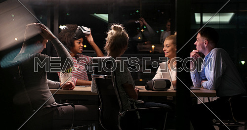 Multiethnic Business team using virtual reality headset in night office meeting  Developers meeting with virtual reality simulator around table in creative office.
