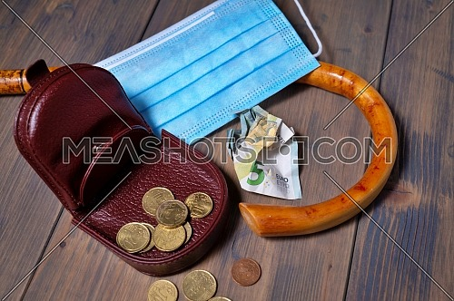 Conceptual Covid-19 flat lay still life with money spilling from an open purse onto a wooden table with cane and surgical mask alongside viewed from above