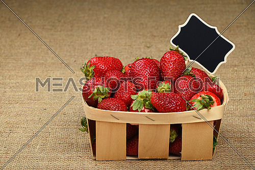 Wicker wooden basket full of red strawberries with chalk blackboard price tag sign on jute burlap canvas background, side view