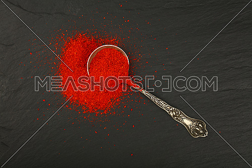 Close up one vintage antique metal spoon full of red chili pepper or paprika powder on background of black slate board, elevated top view, directly above