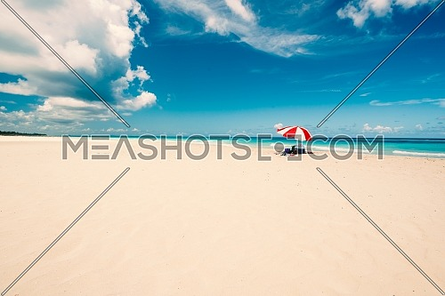 Wonderful beach of Varadero during a sunny day, fine white sand and turquoise and green Caribbean sea,on the right one red parasol,Cuba.concept photo,copy space.Vintage style.
