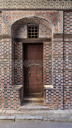 Wooden grunge decorated arched entrance gate with inner small wooden door on wall with black and red bricks with white seam