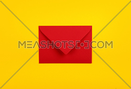 One closed blank red paper envelope over vivid yellow background, flat lay, directly above