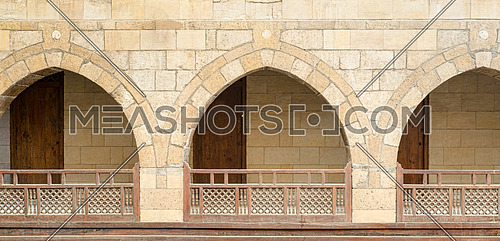 Three arches with interleaved wooden balustrades at the arcade surrounding the courtyard of caravanserai (Wikala) of al-Ghuri, Medieval Cairo, Egypt