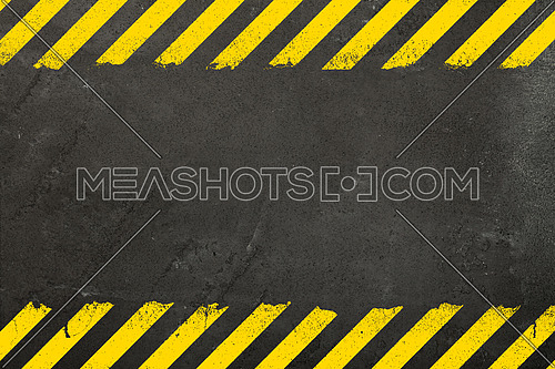 Dark grey oncrete weathered wall background with yellow painted grunge hazard sign stripes and copy space