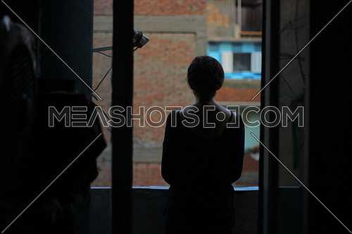 A girl shot from the back in silhouette looking out of a window