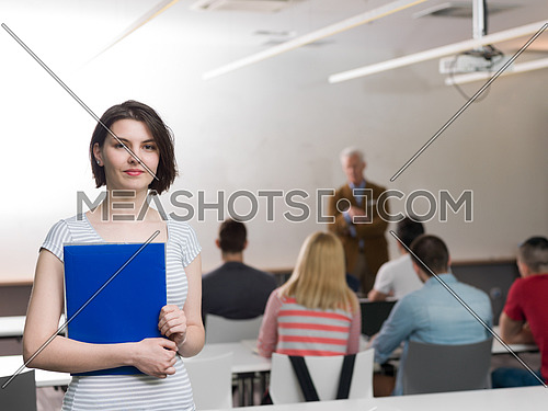 portrait of happy female student holding tablet while teacher teaching students in school classroom