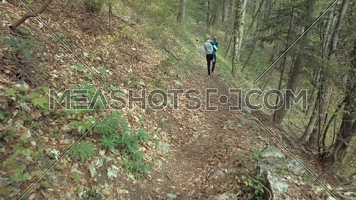 Rear view of mother and her son walking in a mountain path in front of their dog runs