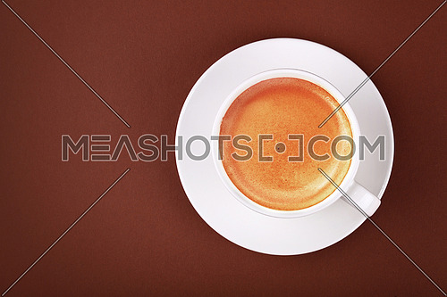 Close up white cup full of espresso coffee with crema froth on porcelain saucer over brown paper background, close up, elevated top view, directly above