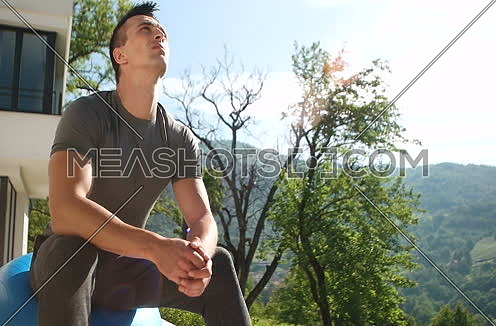 man doing exercise on terace in front of villa