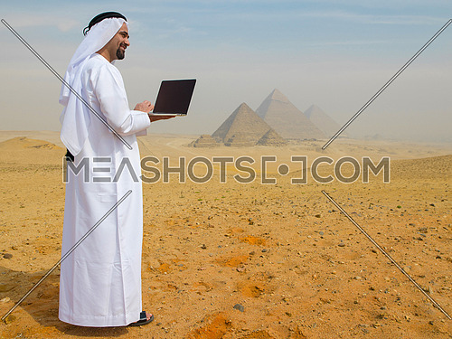 arab business man using laptop computer in desert with great giza pyramids in background