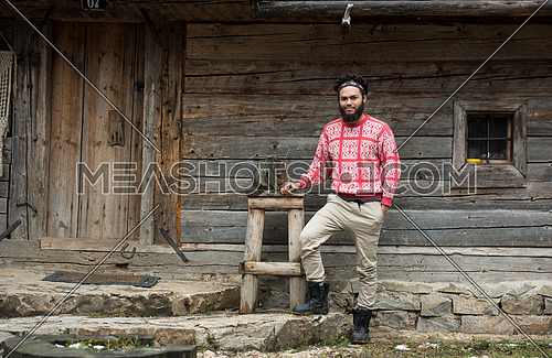 portrait of young hipster man with beard and cat in front of wooden house