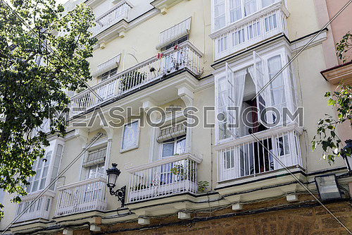 Cadiz Spain- April 1: Detail of balconies and large windows on the time of the nineteenth century, Narrow street with traditional architecture in Cadiz, Andalusia, southern Spain