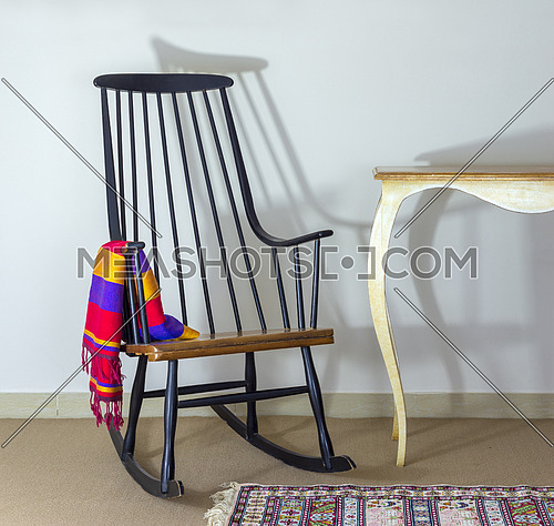 Classic dark brown rocking chair and old style vintage cream painted table on background of off white wall
