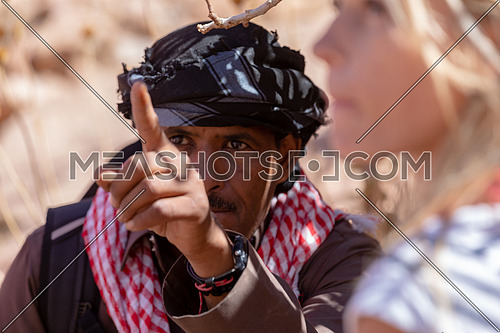 Close up shot for bedouin male gesturing to explore Sinai Mountain for wadi Freij by day.