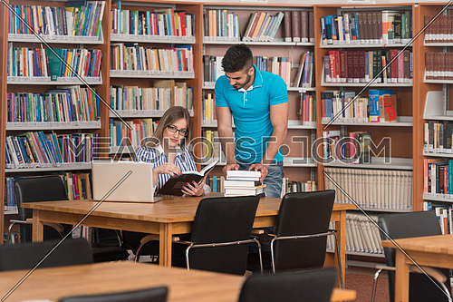 Young Students Working Together In The Library - Shallow Depth Of Field