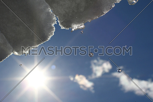 Snow and ice melting and dripping from a roof against the sun and blue skies