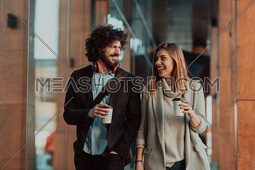 Two business people on a break walk past the industry where they work and drink coffee