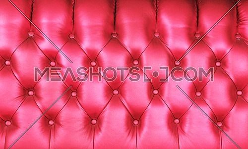 Background texture of pink capitone genuine leather, retro Chesterfield style soft tufted furniture upholstery with deep diamond pattern and buttons, close up