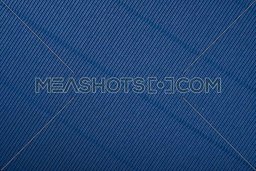 Close up diagonal background pattern texture of dark blue corrugated packaging cardboard