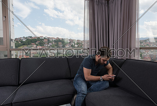young man sitting on sofa and using a mobile phone  near the window at home