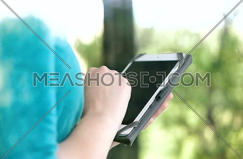 Close up of woman using tablet computer with reflection on the window