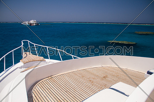 the front of a live a board marine vessel boat showing the wooden deck and the sea