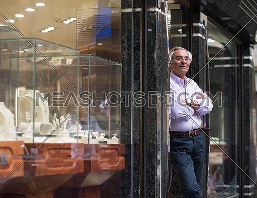 portrait of an elderly middle eastern successful owner who stands at the door of his luxury jewelry store