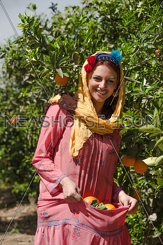 a female egyptian farmer carying oranges in her traditional dress