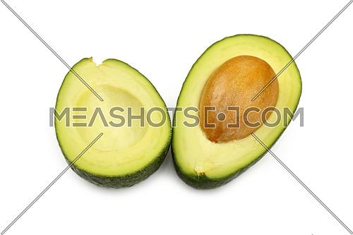 One fresh green ripe avocado cut in two halves with pit stone isolated on white, detail, close up, high angle view, selective focus
