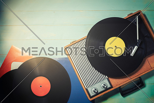Vintage gramophone from the 70s with a vinyl records on green wooden table, top view and copy space.