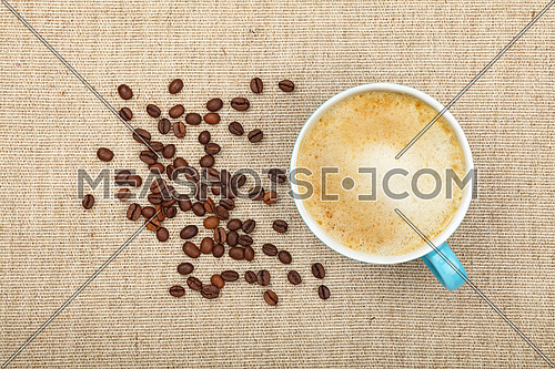 One full latte cappuccino cup and roasted coffee beans on background of linen canvas