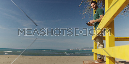 Man operating drone with remote controler by the sea on autumn day