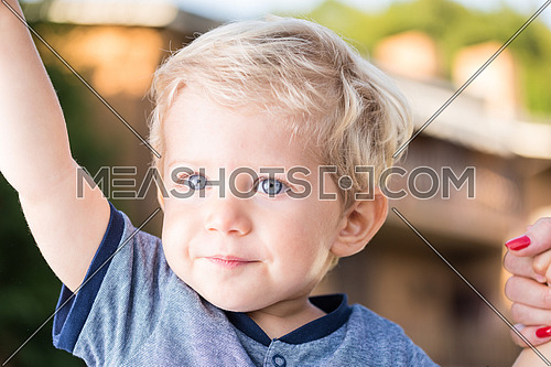 Beautiful baby boy with blue eyes and blond hair holding hands, natural light close up photo