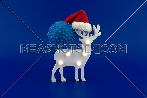Christmas deer scene with blue virus molecule and red Santa hat. Concept of holidays during covid pandemic isolated on blue background