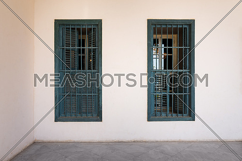 White wall with two grunge windows with wooden green shutters and wrought iron bars and white marble floor