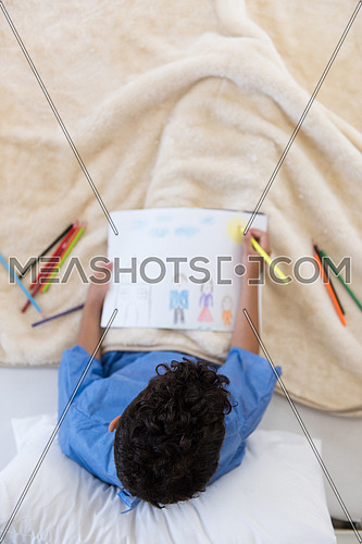 top view of little middle eastern boyl painting home and family at hospital bed