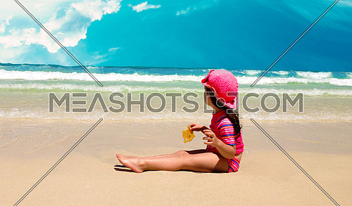 A little  girl sitting at the beach looking towards the ocean