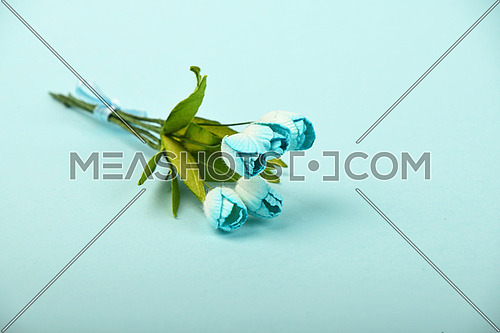 One tiny tulip mulberry paper flowers small bouquet on tender blue background