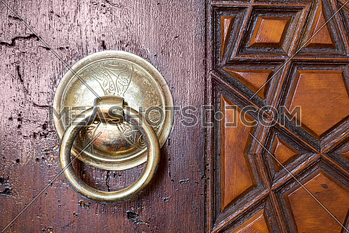 Closeup of antique copper ornate door knocker over an aged wooden door, Suleymaniye Mosque, Istanbul, Turkey