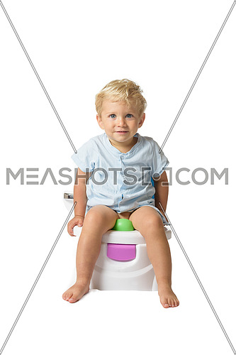 Baby boy, white caucasian smiling and sitting on the potty with white background.