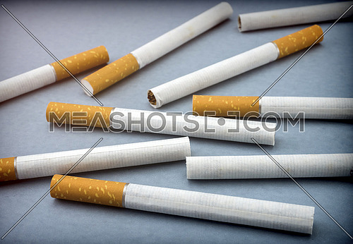 Some cigarettes isolated on a blue background, conceptual image