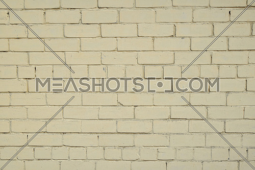 Yellow beige painted pale old brick wall texture background